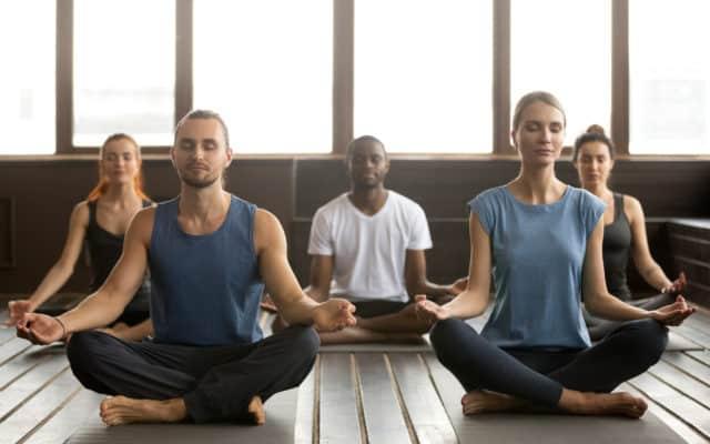 Werknemers in lotushouding tijdens bedrijfsyoga van Yoga op werk